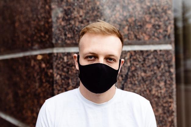 Ritratto maschile. un uomo con una maschera nera. quarantena in città.