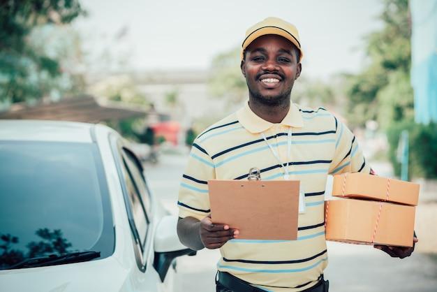Uomo maschio del corriere di consegna postale che tiene consegna scatole e cartone del pacchetto