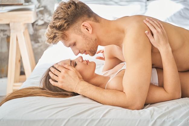 Potere maschile. bella ragazza dai capelli lunghi sdraiata sul letto e guardando negli occhi il suo uomo