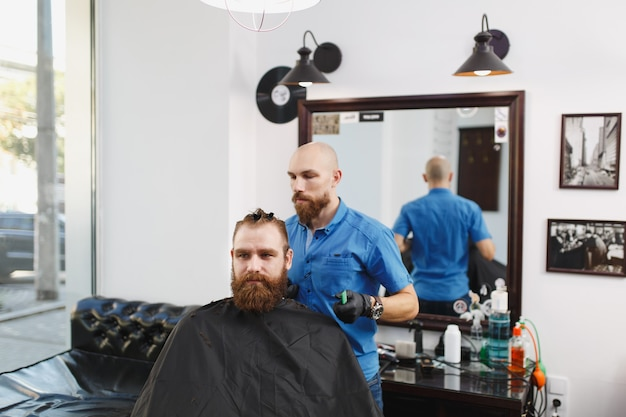 Parrucchiere professionista maschile che serve cliente da clipper