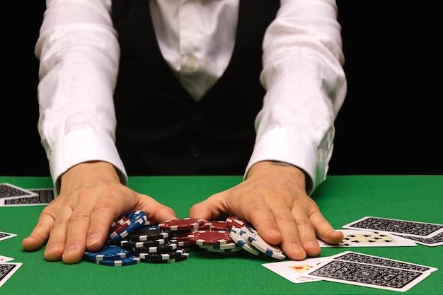 Giocatore di poker professionista maschio che piazza una scommessa giocando a poker in un casinò con panno verde e spazio nero per la copia. concetto rovinato, vincitore online.