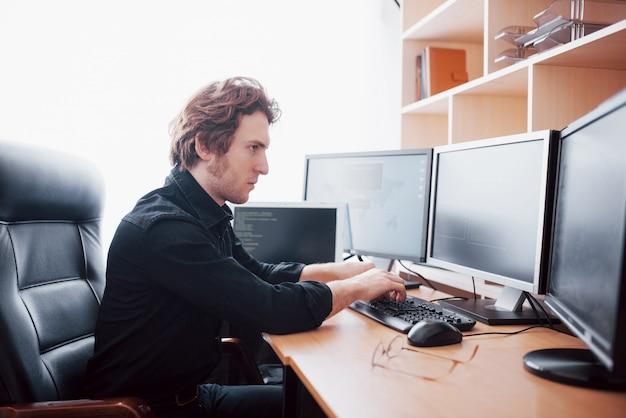Il programmatore maschio che lavora al desktop computer con molti monitor all'ufficio nel software sviluppa la società. tecnologie di programmazione e programmazione del sito web