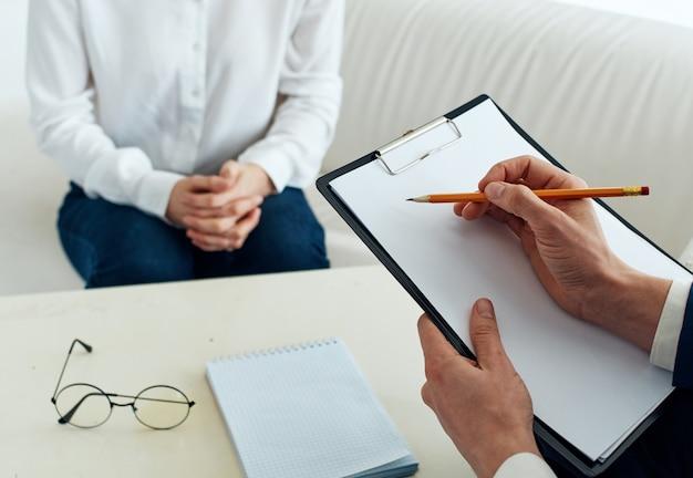 Psicologo maschio con documenti e donna al chiuso