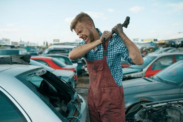 Il riparatore maschio colpisce il vetro con un martello sulla discarica di auto. rottami di automobili, rifiuti di veicoli, rifiuti di automobili, trasporti abbandonati, danneggiati e frantumati