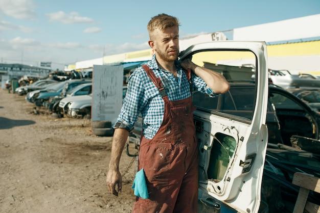 Il riparatore maschio tiene la porta sulla discarica di auto. rottami di automobili, cianfrusaglie di veicoli, rifiuti di automobili. trasporti abbandonati, danneggiati e frantumati, cantiere di demolizione