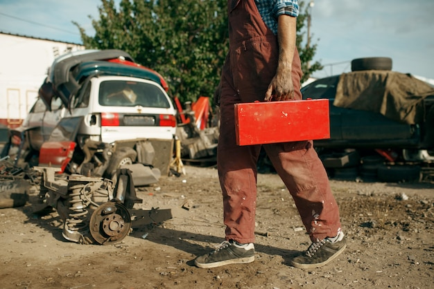 Il riparatore maschio tiene la cassetta degli attrezzi su scrapyard dell'automobile. rottami di automobili, cianfrusaglie di veicoli, rifiuti di automobili. trasporti abbandonati, danneggiati e schiacciati, discarica