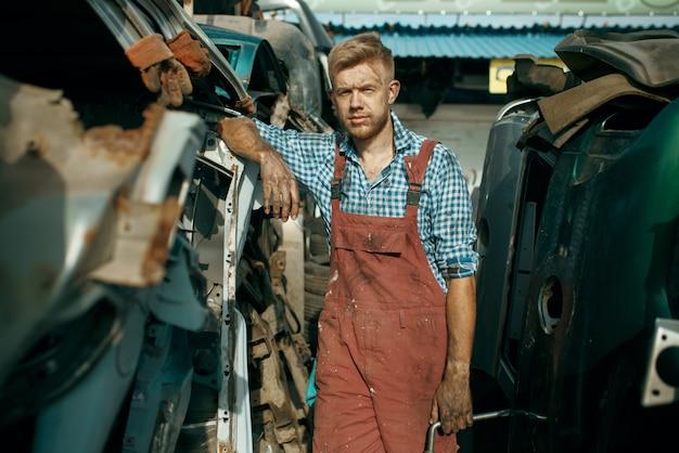 Il riparatore maschio posa sulla discarica di auto. rottami di automobili, rifiuti di veicoli, rifiuti di automobili, trasporti abbandonati, danneggiati e frantumati