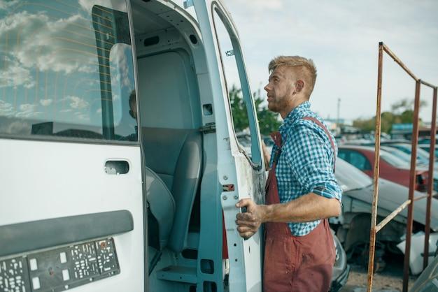 Il riparatore maschio rimuove la porta sul cortile dell'auto. rottami di automobili, cianfrusaglie di veicoli, rifiuti di automobili. trasporti abbandonati, danneggiati e schiacciati, discarica