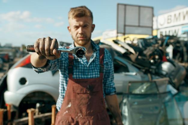 Il riparatore maschio mostra la chiave sul cortile dell'auto. rottami di automobili, cianfrusaglie di veicoli, rifiuti di automobili. trasporti abbandonati, danneggiati e schiacciati, discarica