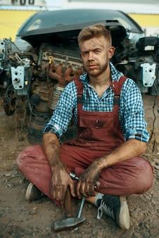 Riparatore maschio seduto per terra sulla discarica di auto. rottami di automobili, rifiuti di veicoli, rifiuti di automobili, trasporti abbandonati, danneggiati e frantumati
