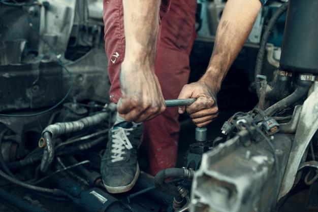 Il riparatore maschio cerca di svitare la parte sulla discarica di auto. rottami di automobili, rifiuti di veicoli, rifiuti di automobili, trasporti abbandonati, danneggiati e frantumati