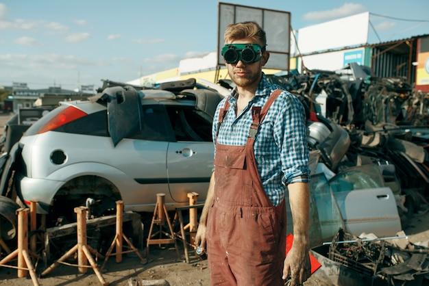 Riparatore maschio in vetri di saldatura su scrapyard auto. rottami di automobili, cianfrusaglie di veicoli, rifiuti di automobili. trasporti abbandonati, danneggiati e schiacciati, discarica