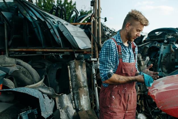 Riparatore maschio con l'asciugamano sulla discarica di auto. rottami di automobili, cianfrusaglie di veicoli, rifiuti di automobili. trasporti abbandonati, danneggiati e frantumati, cantiere di demolizione