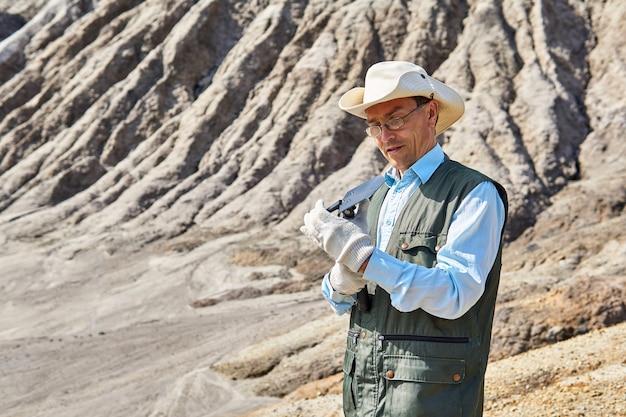 Ricercatore maschio prepara per il lavoro una pala pieghevole contro un paesaggio desertico