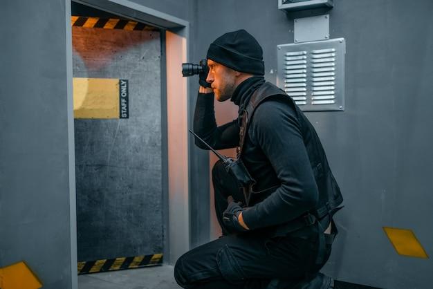 Ladro maschio in uniforme nera tiene pistola e lanterna