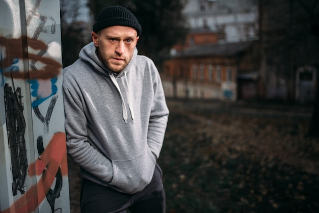 Rapinatore maschio in attesa di vittima sulla strada di notte. concetto di criminalità, pericolo di attacco di rapina