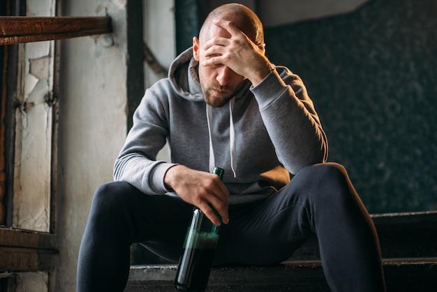 Ladro maschio con una bottiglia di alcol si siede sulle scale. bandito di strada in attesa di vittima. concetto di criminalità, pericolo di attacco di rapina