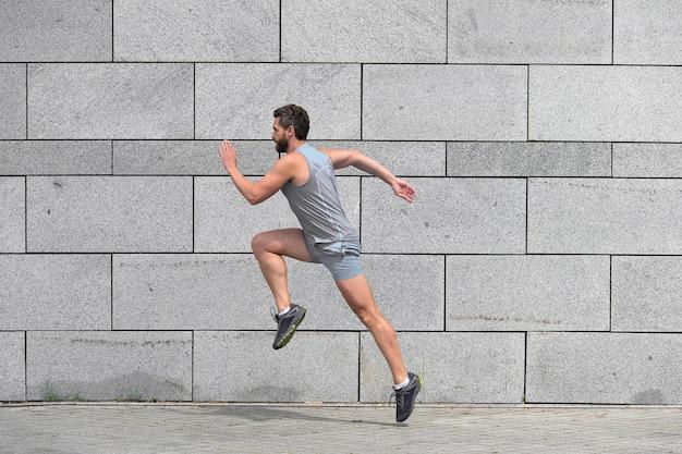 Uomo corridore maschio che corre verso il successo sportivo lottando per la vittoria abbigliamento sportivo uomo attivo