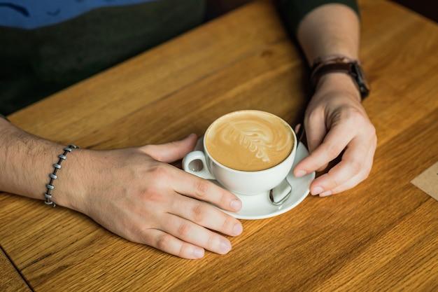 Mani del maschio che tengono una tazza di caffè cappuccino, tavolo in legno