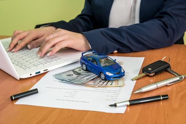 Le mani del maschio firmano sul modulo di richiesta del contratto auto e calcolatrice, dollaro, auto