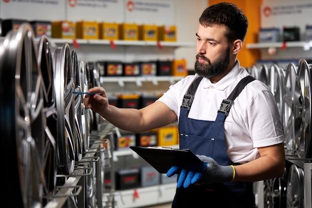 Venditore maschio nel negozio di auto a prendere appunti, controllare il documento ed esaminare le caratteristiche, guardando il rack con cerchi auto