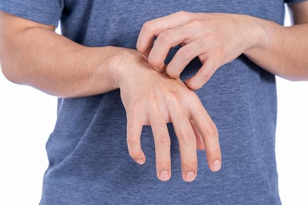 Il maschio che graffia la sua mano ha isolato il fondo bianco