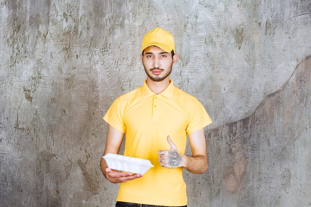 Agente di servizio maschio in uniforme gialla che tiene una scatola bianca da asporto e mostra un segno di divertimento enjoyment