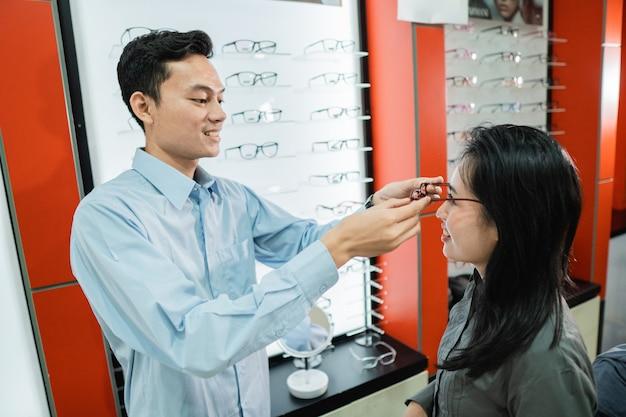 Il commesso maschio mette gli occhiali alla cliente donna mentre si trova dall'ottico