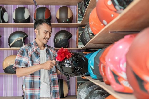 Il commesso maschio sta pulendo un casco con uno spolverino nel negozio di elmetti