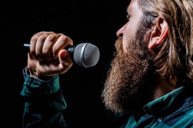 Maschio che canta con un microfono. uomo con la barba che tiene un microfono e canta. l'uomo barbuto in karaoke canta una canzone in un microfono. il maschio frequenta il karaoke.