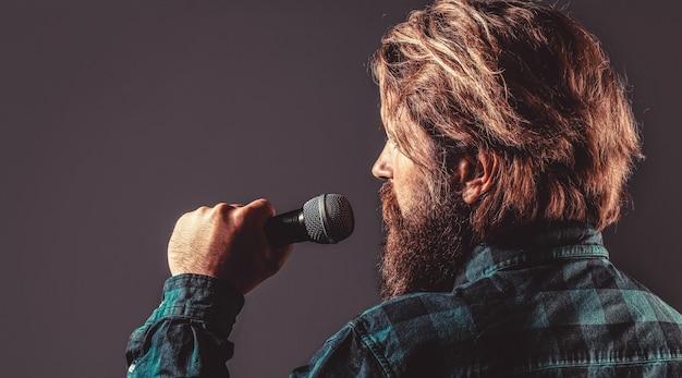 Canto maschile con microfoni. uomo con la barba che tiene un microfono e canta. l'uomo barbuto al karaoke canta una canzone in un microfono.