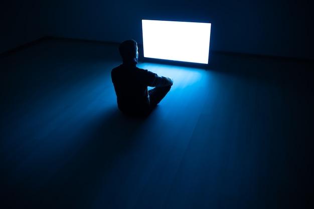 Il maschio seduto nella stanza buia davanti a uno schermo bianco