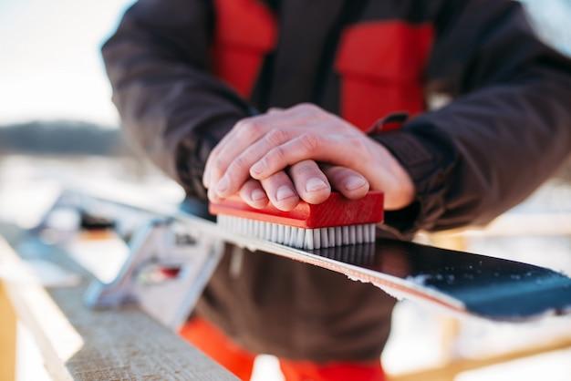 Mani di sciatore maschio prepara gli sci per l'equitazione. sport attivo invernale, stile di vita estremo. sci alpino