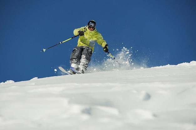 Sciatore maschio in abiti sportivi gialli a cavallo lungo il pendio in georgia, gudauri