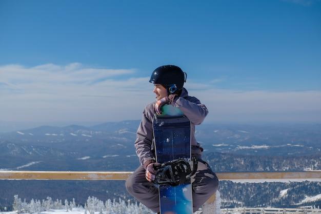 Snowboarder maschio in un casco tiene uno snowboard sullo sfondo delle montagne