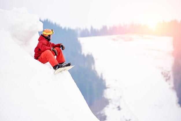 Snowboarder maschio sulla cima della collina nevosa