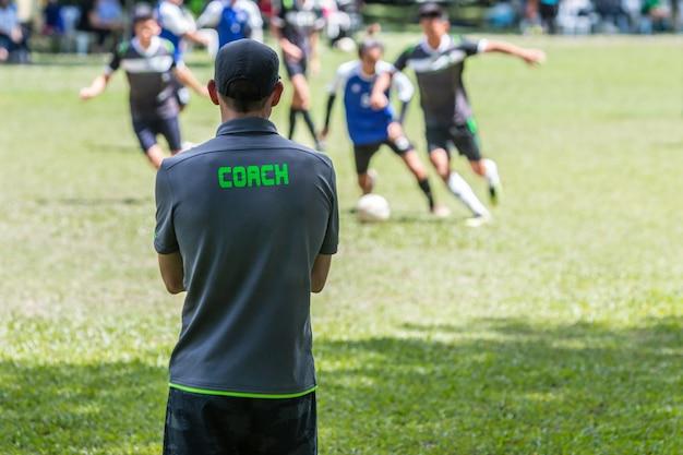 Allenatore di calcio o di calcio maschile in piedi sulla linea laterale a guardare il suo gioco di squadra