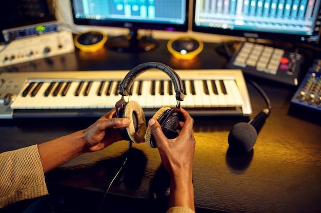 L'ingegnere del suono maschio tiene le cuffie alla console di mixaggio, l'interno dello studio di registrazione sullo sfondo. sintetizzatore e mixer audio, posto di lavoro del musicista, processo creativo