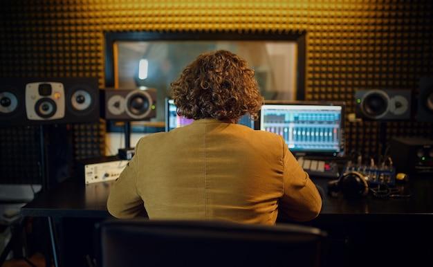 Ingegnere del suono maschio alla console di mixaggio, vista posteriore, interno dello studio di registrazione sullo sfondo. sintetizzatore e mixer audio, posto di lavoro del musicista, processo creativo