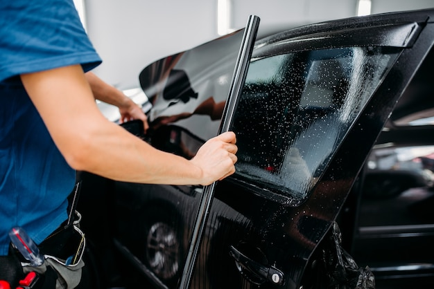 Specialista maschile che applica pellicola oscurante per auto, processo di installazione, procedura di installazione di vetri auto colorati