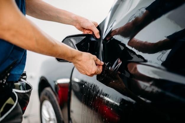 Specialista maschile lavora con auto, processo di installazione di pellicole oscuranti, procedura di installazione di vetri auto colorati glass
