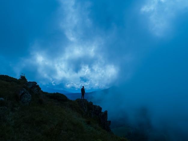 Il maschio in piedi sulla montagna nebbiosa. sera notte