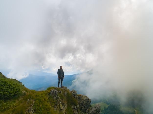 Il maschio in piedi sulla montagna nebbiosa