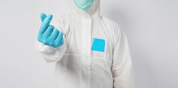 Maschio in piedi nella suite dpi e maschera facciale che fa un segno con la mano mini cuore su sfondo bianco.