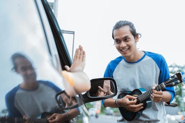 Musicista di strada maschio che elemosina soldi