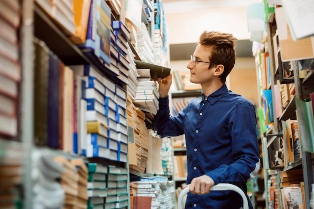 Studente maschio in cerca del libro necessario su numerosi scaffali della biblioteca
