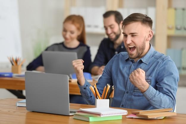 Studente maschio con il computer portatile che fa i compiti in aula