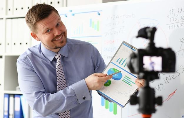 Maschio in giacca e cravatta mostra grafico grafico statistiche