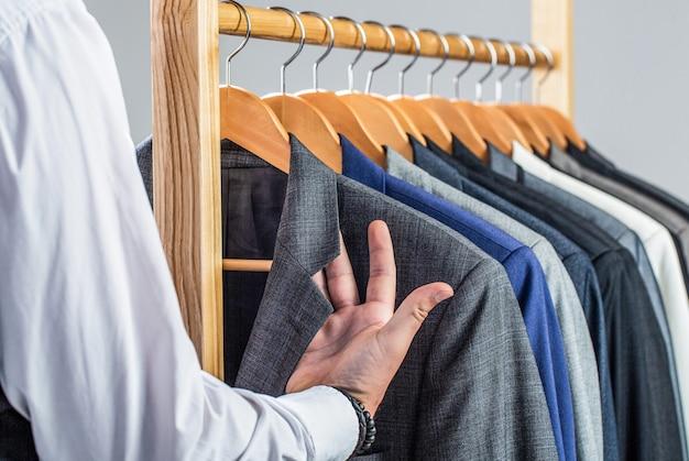 Abiti maschili appesi in fila. abbigliamento uomo, boutique. abito da uomo, sarto nel suo laboratorio. moda uomo in costume classico. sarto, sartoria. abito da uomo alla moda.