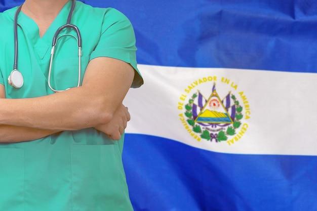 Maschio chirurgo o medico con lo stetoscopio sullo sfondo della bandiera di el salvador